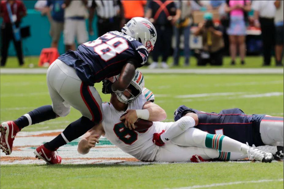 Os linebackers dos Patriots, Jamie Collins Sr. e Elandon Roberts com o sack em Ryan Fitzpatrick. Créditos: Lynne Sladky / AP Images
